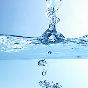 A drop of water plunges into a body of water, creating a ripple effect